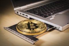 Bitcoin guld- mynt över ett CD drev för bärbar dator` s Royaltyfri Foto