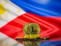 Bitcoin guld- mynt och defocused flagga av Filippinernabakgrund Faktiskt cryptocurrencybegrepp royaltyfria bilder