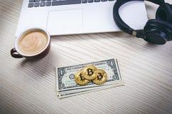 Bitcoin guld- mynt på sedlar för en dollar Kontorsbakgrund Kopp kaffe, vit bärbar dator, mobiltelefon och pengar Pengarjämvikt Royaltyfria Bilder