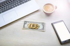 Bitcoin guld- mynt på sedlar för en dollar Kontorsbakgrund Kopp kaffe, vit bärbar dator, mobiltelefon och pengar Pengarjämvikt Arkivfoto