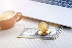 Bitcoin guld- mynt på sedlar för en dollar Kontorsbakgrund Kopp kaffe, vit bärbar dator, mobiltelefon och pengar Pengarjämvikt Arkivbilder