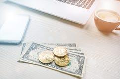 Bitcoin guld- mynt på sedlar för en dollar Kontorsbakgrund Kopp kaffe, vit bärbar dator, mobiltelefon och pengar Pengarjämvikt Fotografering för Bildbyråer
