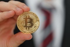 Bitcoin in the hand. Businessman showing Gold Bitcoin in the hand stock image