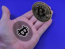 Bitcoin in hand. Bitcoin floating above open hand Stock Photo