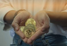 Bitcoin in the girl`s hand. It is the newest currency in the wor. Bitcoin in the hand. It is the newest currency in the world Royalty Free Stock Photography