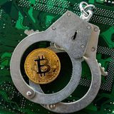 Bitcoin and handcuffs on a computer chip, top view royalty free stock photo
