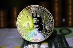 Bitcoin hermoso BTC en el fondo de las monedas euro del billete de banco y de oro imagen de archivo libre de regalías