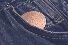 Bitcoin i blå jean: finans- och ekonomibegrepp royaltyfri fotografi