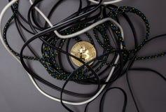Bitcoin i ett rede av kablar arkivbild