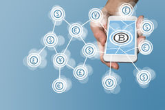 Bitcoin icon displayed on touchscreen of modern smart phone as example for fin-tech company Royalty Free Stock Images