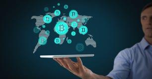 Bitcoin-Ikonen auf Weltkarte mit dem Mann, der Tablette hält Lizenzfreie Stockfotografie