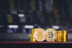 Bitcoin invente la pile et deux pièces de monnaie de bit se reposant dans l'avant avec le fond numérique de diagramme de graphiqu images stock