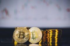Bitcoin invente la pile et deux pièces de monnaie de bit se reposant dans l'avant avec le fond numérique de diagramme de graphiqu photographie stock