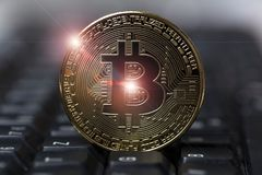 Bitcoin on an keyboard. A bitcoin on an keyboard Stock Photo