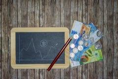 Bitcoin-Kurs auf cahalkboard mit Banknoten, Geldmünzen und Bleistift stockfotos