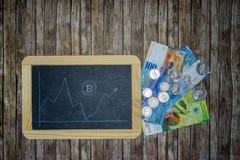 Bitcoin-Kurs auf cahalkboard mit Banknoten und Geldmünzen lizenzfreies stockfoto