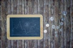 Bitcoin-Kurs auf Tafel mit Geldmünzen stockfoto