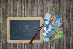 Bitcoin kurs na cahalkboard z banknotami, pieniądze monetami i ołówkiem, Zdjęcia Stock