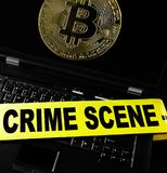 Computer bitcoin crime. Bitcoin on a laptop with crime scene tape Royalty Free Stock Image