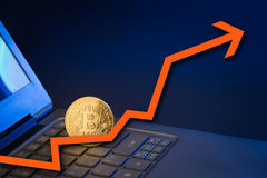 Bitcoin on laptop keyboard with arrow pointing up Stock Images