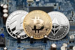 Bitcoin litecoin ethereum crypto currency computer mining concep. Bitcoin litecoin ethereum silver and golden coin on blue motherboard chip digital mining Stock Images