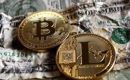 Bitcoin and Litecoin over dollar banknotes. Bitcoin and Litecoin over crushed dollar banknotes. Cryptocurrency conspiracy concept Royalty Free Stock Photo