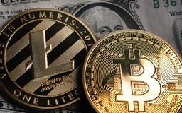 Bitcoin and Litecoin over dollar banknotes. Royalty Free Stock Photography