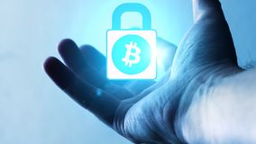 A bitcoin lock that orbits on the palm of a man`s hand stock photo