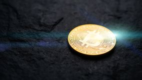 Bitcoin logo on flat black stone with light flare. cyber cryptocurrency money concept.  royalty free stock image