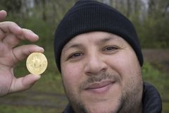 bitcoin lover with a gold coin in your hand , funny miner with BTC near the face stock photo