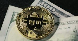 Bitcoin-Münze auf den Dollarbanknoten, die auf einen schwarzen Hintergrund spinnen stock video