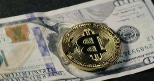 Bitcoin-Münze auf den Dollarbanknoten, die auf einen schwarzen Hintergrund spinnen stock footage