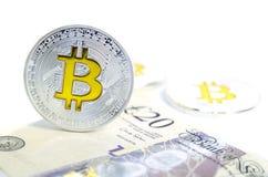 Bitcoin-Münze, die auf Papierpfundrechnung legt Stockfotografie