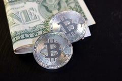 Bitcoin-Münze und ein Dollar auf schwarzem Hintergrund Lizenzfreies Stockfoto