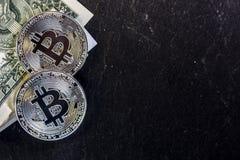 Bitcoin-Münze und ein Dollar auf schwarzem Hintergrund Lizenzfreie Stockfotos