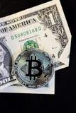 Bitcoin-Münze und ein Dollar auf schwarzem Hintergrund Stockfotos