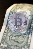 Bitcoin-Münze und ein Dollar auf schwarzem Hintergrund Stockbild