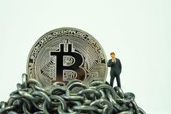 Bitcoin-Münze und Miniaturgeschäftsmann, die an Zukunft pri denken Lizenzfreies Stockbild