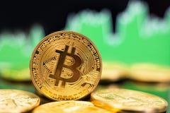 Bitcoin-Münzen mit grünem Diagramm lizenzfreies stockfoto