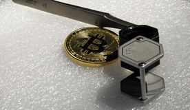 Bitcoin magnifier and tweezers. A close up of a bitcoin, a magnifier, and tweezers Royalty Free Stock Photos