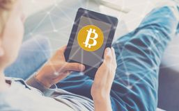 Bitcoin with man using a tablet Royalty Free Stock Photo