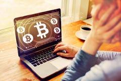 Bitcoin med mannen som anv?nder en b?rbar dator arkivbild
