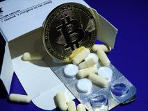 Bitcoin and medicine. A bitcoin with box of medicine, capsules and blister packs of pills Stock Photography