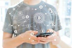 Bitcoin met de mens die een smartphone gebruiken Royalty-vrije Stock Foto's