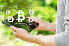 Bitcoin met de mens die zijn tablet houden royalty-vrije stock afbeeldingen