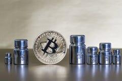 Bitcoin met gewichten en gegraveerd met symbolen van dollar, die de groei en de daling tonen stock foto