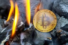 Bitcoin coin is burning with blue flame. It means hot price or value and high exchange rate of crypto currency on market. Bitcoin metal coin is burning with royalty free stock photo