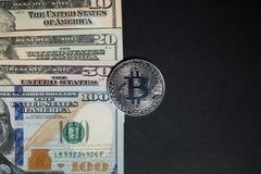 Bitcoin in mezzo alle banconote in dollari americane fotografie stock