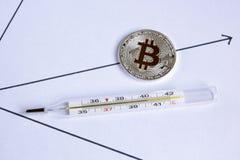 Bitcoin miente en el diagrama al lado de un termómetro con un alto te Imagen de archivo