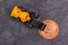 Bitcoin and miniature excavator, symbol of electronic virtual money and mining cryptocurrency stock images